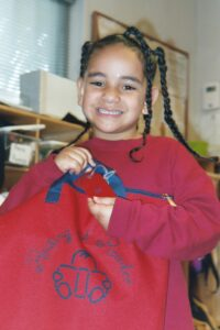 Girl_smiling_and_holding_red_RAR_book_bag